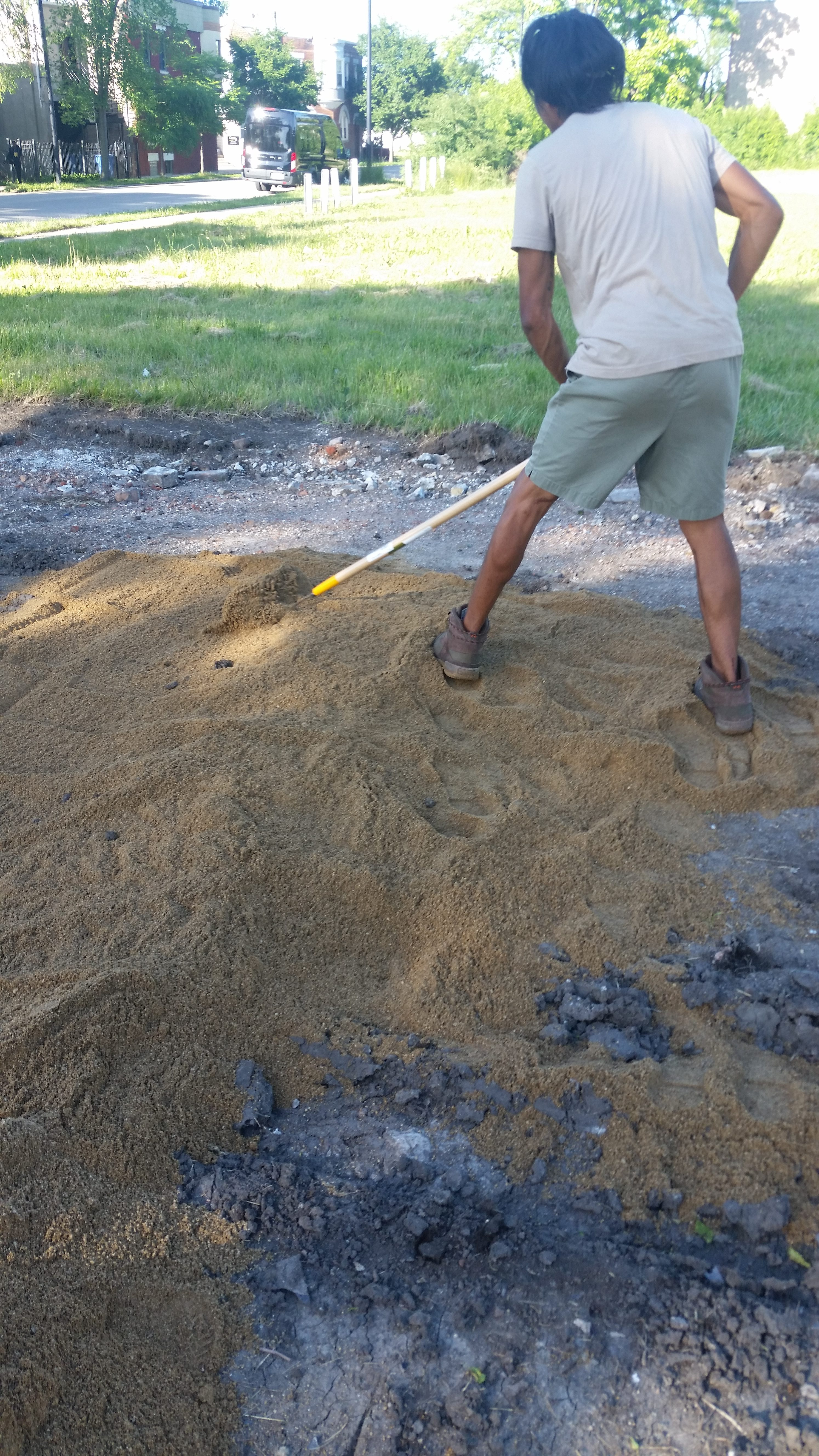 raking out first layer of sand for outdoor bed
